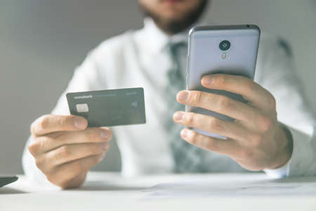 Businessman uses credit card and a smartphone. Mobile phone. Online payment. Shopping online. Close up telephone. Office work concept.