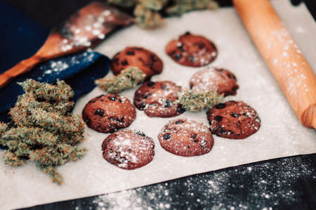 Sweets with weed. Chocolate cookies with marijuana. Sweets with cannabis. Cannabis buds on a black background. Baking with the addition of CBD.