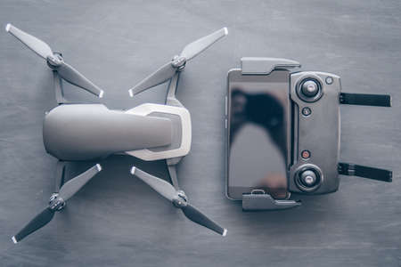 Innovation photography concept. Mate color. A new black drone on a black table. The concept of using drones in life and industry. Top view Remote and smartphone macro Details. Copy space. Stok Fotoğraf