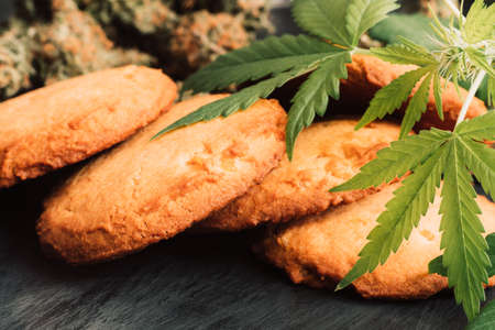 Cannabis buds on a black background. Baking with the addition of CBD. Sweets with weed. Cookies with marijuana. Sweets with cannabis.