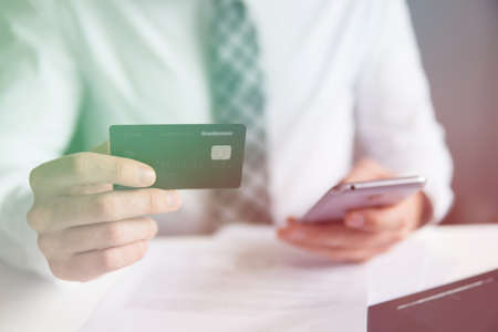 Payment of goods online. Online trading on the currency exchange. Young businessman with a bank credit card in his hands. Smartphone and Internet Commerce. Online payments through the phone.
