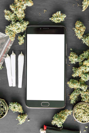 Smartphone with green screen for hroma key in hand man, chromakey against the background of cannabis flowers
