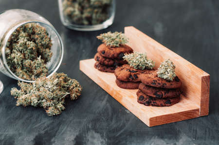 Cannabis buds on a black background. Baking with the addition of CBD. Sweets with weed. Chocolate cookies with marijuana. Sweets with cannabis. Stock Photo