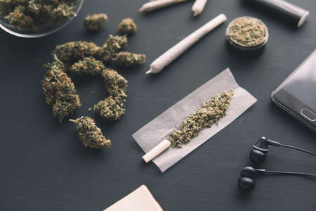 marijuana buds on black table, close up, grinder in hand with fresh Cannabis, joint with weed, Stok Fotoğraf