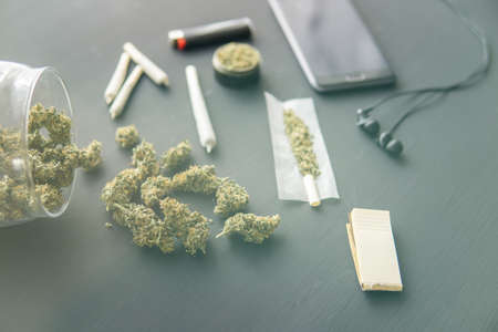 marijuana buds on black table, close up, grinder in hand with fresh Cannabis, joint with weed, light leaks color tones