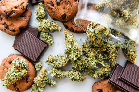 Cookies with cannabis and buds of marijuana on the table. Treatment of medical marijuana for use in food, white background.Cookies with cannabis herb CBD. Banco de Imagens - 122394203