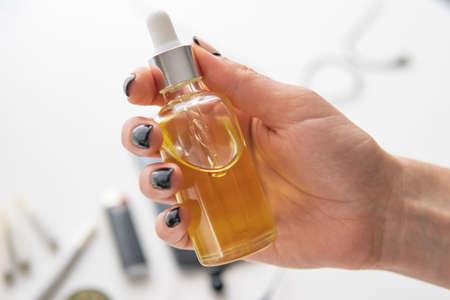estratto di marijuana su sfondo bianco, prodotto infestante, primo piano, concetto di canapa medica, olio di cannabis CBD in pipetta a mano da donna, Archivio Fotografico