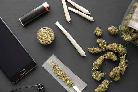 grinder in hand with fresh marijuana, close up, joint with weed, Cannabis buds on black table, 版權商用圖片