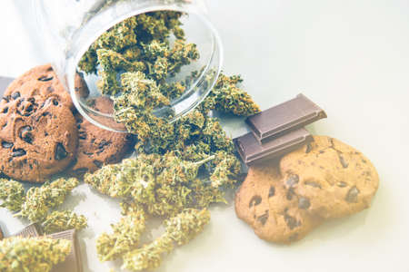 Cookies with cannabis and buds of marijuana on the table. Cookies with cannabis herb CBD. Treatment of medical marijuana for use in food, white background. light leaks Imagens