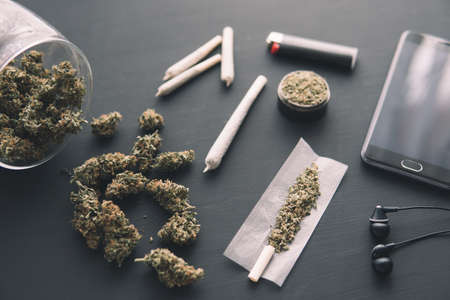 grinder in hand with fresh Cannabis, joint with weed, close up, marijuana buds on black table,