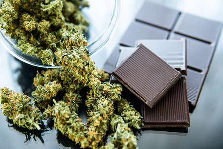 Konzept der Schokolade mit Cannabiskraut CBD. Behandlung von medizinischem Marihuana zur Verwendung in Lebensmitteln, schwarzer Hintergrund. Schokolade mit Cannabis und Marihuanaknospen auf dem Tisch.