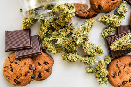 Cookies with cannabis herb CBD. Cookies with cannabis and buds of marijuana on the table. Treatment of medical marijuana for use in food, white background. 免版税图像
