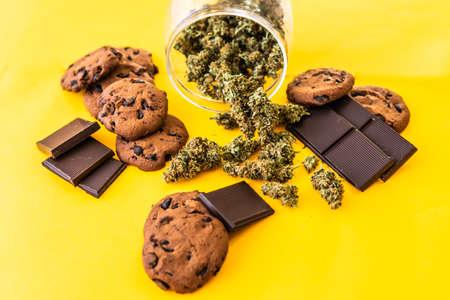 Treatment of medical marijuana for use in food, yellow background. Cannabis CBD herb Chocolate and Cookies. Cookies and Chocolate with cannabis and buds of marijuana on the table. 免版税图像
