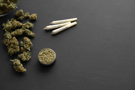 Cannabis buds on black table, joint with weed, grinder with fresh marijuana, top view close up,