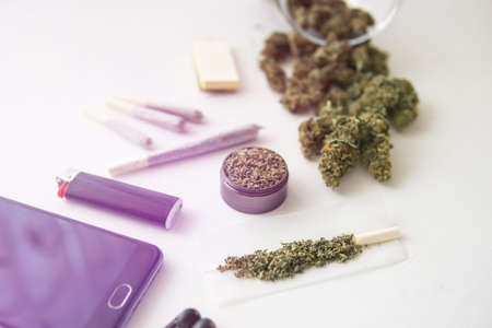 close up, joint with marijuana, grinder with fresh weed , Cannabis buds on black table, light leaks color tones