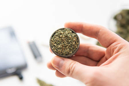 grinder with fresh marijuana in hand, Cannabis weed buds on white table, marijuana, close up