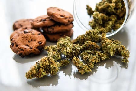 Cookies with cannabis herb CBD. Cookies with cannabis and buds of marijuana on the table. Treatment of medical marijuana for use in food, white background. Banco de Imagens