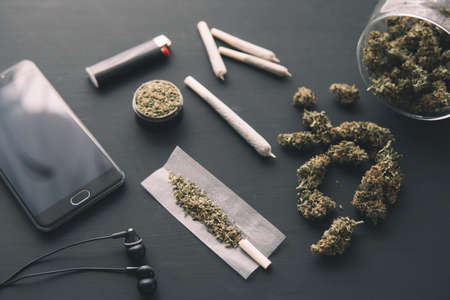 grinder in hand with fresh Cannabis, close up, marijuana buds on black table, joint with weed,