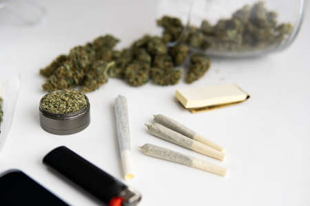 Cannabis buds on black table, grinder with fresh weed, close up, joint with marijuana, Banco de Imagens
