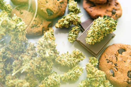 Treatment of medical marijuana for use in food, white background. Cookies with cannabis herb CBD. Cookies with cannabis and buds of marijuana on the table. light leaks Banco de Imagens