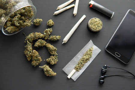 grinder in hand with fresh marijuana, close up, joint with weed, Cannabis buds on black table, Banco de Imagens