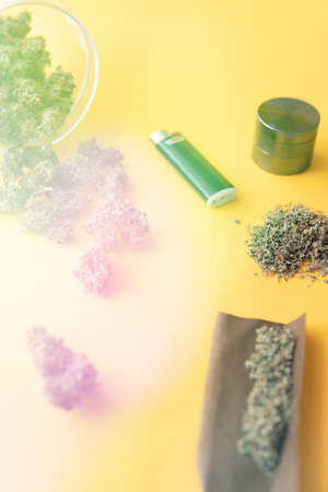 CBD and THC on buds in cannabis. Top view. Cannabis buds in hand on yellow background Background for Copy space. Hemp legalisation. Blunt and Lighters. Herb grinder Fresh marihuana. light leaks