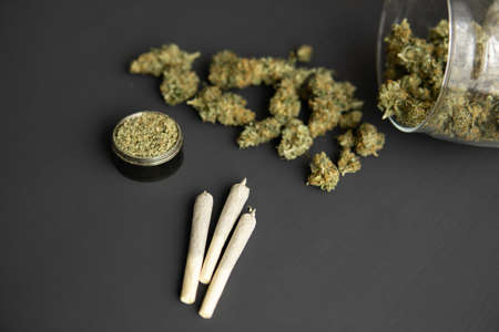 Cannabis buds on black table, grinder with fresh marijuana, top view, close up, joint with weed,
