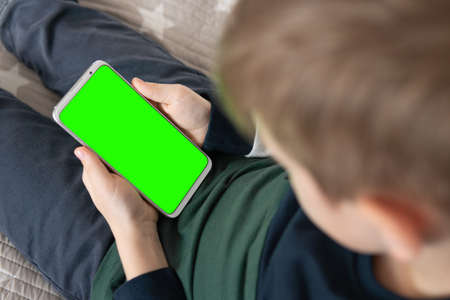 Phone a for keying is holding kid. Smartphone with a hromakey in the hands of a child. close up top view Smartphone with a green screen in hand child .