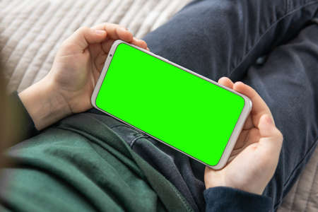 Smartphone with a green screen in hand child . Smartphone with a hromakey in the hands of a child top view close up. Phone a for keying is holding kid.