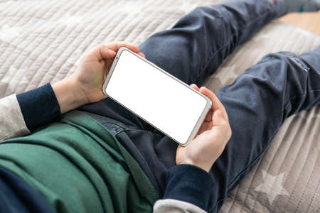 Smartphone with a white screen in hand child. Phone a for mock up is holding kid. Smartphone with a mock up in the hands of a child. top view close up Stock Photo