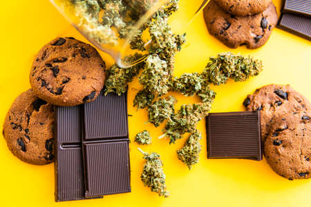 Treatment of medical marijuana for use in food, yellow background. Cookies and Chocolate with weed and buds of marijuana on the table. Cannabis CBD herb Chocolate and Cookies. Standard-Bild