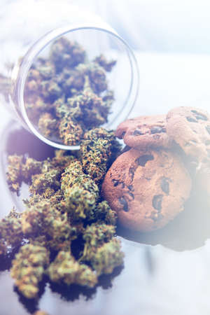 Concept of cooking with cannabis herb. Cookies with cannabis and buds of marijuana on the table. Treatment of medical marijuana for use in food, On a black background. Vertical shot Stock Photo