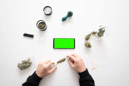Smartphone mockup Green screen. White background. Top view. Sativa medical health. The sugar pot leaves on buds. Mans hands marijuana bud. Standard-Bild