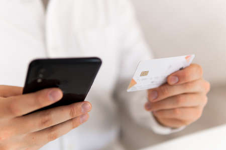 Closeup of young man making Online shopping concept in morning light. man hands using smartphone and holding credit card with social Payment online shopping smartphone at working place. Banque d'images