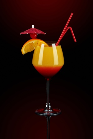 Sunrise coctail with orange, cherry, umbrella and straw