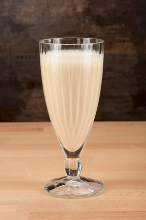 A glassfull of fresh cold banana shake on a wooden table. photo