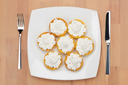 plateful: A plateful of tart shells filled with cheese, with fork and knife on a wooden table.