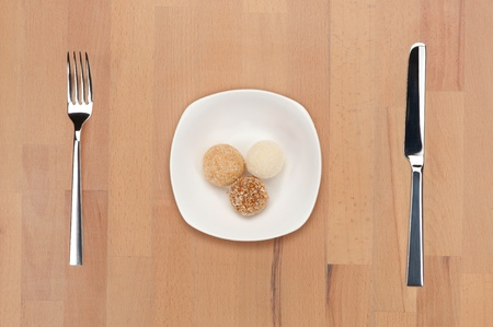 gulab: A white plate with three balls of traditional Indian sweets - gulab - on a wooden table with fork and khife.