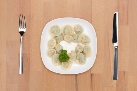 A plate with vegetarian ravioli decorated with parsley on a wooden table with fork and knife. photo