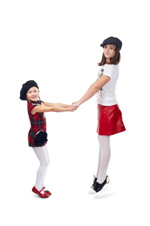 Two girls in fashionable clothes jumping on white background.  photo