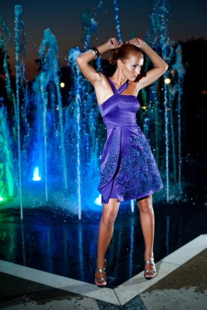 Beautiful girl dancing at outdoor water fountain in a night photo