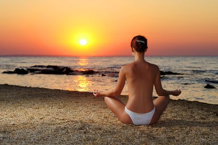 Girl meditating in sunrise photo
