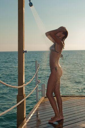 nue plage: Belle femme prenant une douche relaxante