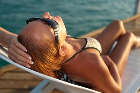 Beautiful woman lying on a deckchair at the beach photo