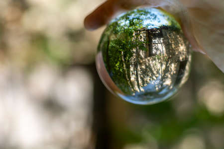 Italian summer landscape, seen through a small crystal ball, hand of man holding the lensball, ancient religious constructions Stock Photo