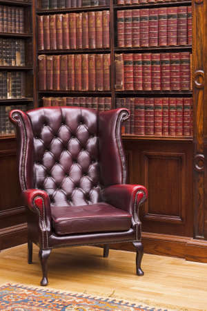 Traditional Chesterfield chair in classical library room photo