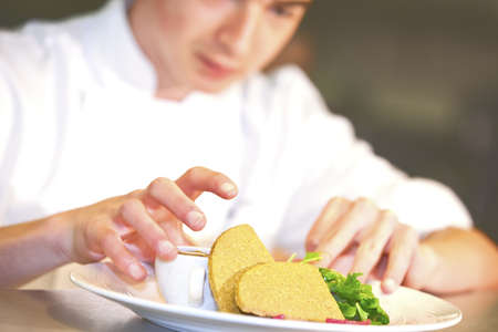 garnishing: Closeup of chef adding finishing touch on his dish bere it goes on the table  Stock Photo