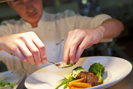 Closeup of chef adding finishing touch on his dish befe it goes on the table
