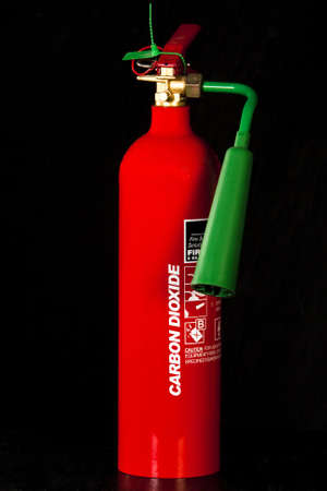 fire hazard: Fire extinguisher isolated on black background Stock Photo