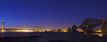 Forth Road och järnvägsbroar panoramabild i kvällsljus.